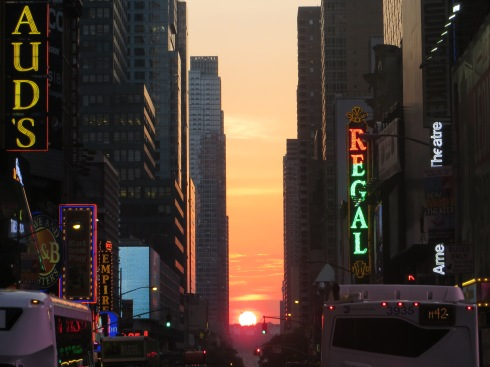 The setting sun aligns with the Manhattan skyscrapers